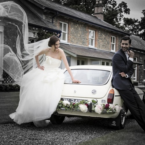 Our bride & groom with their vintage bridal car infront of the estate